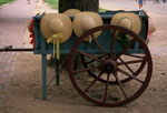 Straw hats displayed on a wooden cart.