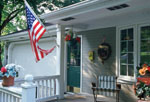 Attractive small town front porch with American flag flying.