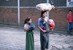 Guatemalan woman with her daughter and baby as she carries food on her head.