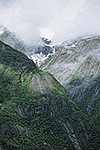 Rain forest, mist, and snowfields in the high cliffs along the Tracy Arm fjord, Tracy Arm-Fords Terror Wilderness, Tongass National Forest, Alaska