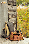 A fishing rod, wicker creel, and hip boots on the stoop of a weathered homestead cabin, Lake Clark National Park, Alaska