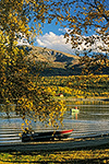 A small boat on Lake Clark with fall color in birch trees, Port Alsworth, Lake Clark National Park, Alaska