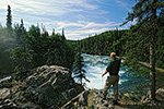 A fisherman surveys the Tanalian River from a ledge above Tanalian Falls, Lake Clark National Park, Alaska