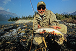 A fly fisherman lands a lake trout at Kontrashibuna Lake, Lake Clark National Park, Alaska