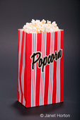Red and white striped bag of popcorn in a studio setting