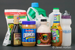 Various polyethylene polymers, including PETE: marinade, peanut butter, salad dressing, HDPE: maple syrup, milk, plastic shopping bag, Cascade dishwashing detergent, and LDPE: water bottle, peas frozen vegetables bag, taken in a studio setting