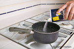 Pouring salt into a pot with boiling water on a stove in a kitchen