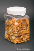 Clear plastic covered container of snack mix made up of pieces of various shapes and sizes, on a black background.  Snack mix consists of a variety of pretzels, croutons, crackers, and cereal.