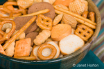 Bowl of snack mix made up of pieces of various shapes and sizes, sitting on a turquoise napkin on a stiped placemant.  Snack mix is made up of various kinds of pretzels, crackers, croutons and cereal.