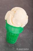 Scoop of vanilla ice cream on a green ice cream cone on a dark tile counter top