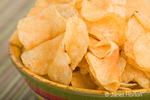 Potato chips in a green bowl with yellow, red & purple stripes, on a striped placemat
