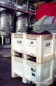 Bins of grape hulls and a row of stainless steel wine storage tanks at Stags Leap Winery.