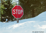 Stop sign buried in deep snow in Sierra Nevada mountains
