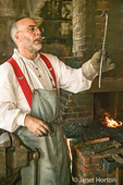 Blacksmith, standing at the forge giving a demonstration on making an iron piece and shoing a finished decorative hook