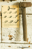 Antique blacksmith hammer with a straight pein head hanging on a wall, taken in the Blacksmith Shop.  Also shown is a sign illustrating the types of heads used on a hammer.