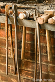 Blacksmith tools (hammers, tongs, and swages) hanging by the forge
