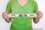 26 year old woman holding a digitally stretched wide dollar bill, to illustrate stretching your money by using it wisely