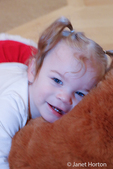 13-month old Lily playing with a large stuffed bear.  Bear needs a big hug!