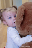13-month old girl hugging a large stuffed bear