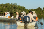 Tourists waiting for a jaguar to move, marking time in the tour boats on a river safari in the Pantanal area of Brazil.
