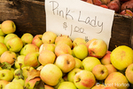 Pink Lady apples for sale at a fruit stand.