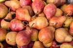 Red Bartlett pears for sale at a fruit stand.