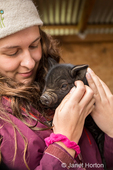Teenage girl cuddling a two week old piglet.  (For editorial use only)