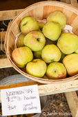 Heirloom Northern Spy apples for sale at a fruit stand.