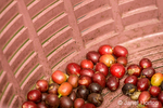 Coffee fruit / berries / cherries in a basket.  Each cherry contains two seeds that are surrounded by a soft layer of mucilage and a thin skin known as the parchment.