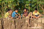 Six bored young boys sitting on the steep riverbank of the Maranon river, an Amazon river tributary. (For editorial use only)