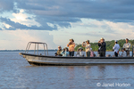 Tourists in a skiff watching for dolphins in the Maranon river, an Amazon tributary.