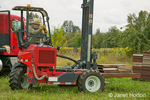 Man using his Moffett Mounty forklift to move pallet with hive covers.