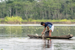Young boy checking his fishing nets in the Ucayali River in the Amazon basin.