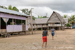 Native people walking beside their homes built on stilts in the village of Puerto Miguel.