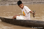 Boy in a dugout canoe holding a Vermiculated Sailfin Catfish (Pterygoplichthys disjunctivus) he had just caught.