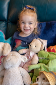 One year old girl sitting on a sofa with her stuffed animals.