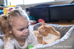 """Almost 2 year old girl in a stare contest with her cat """"Kita"""" staring at each other, reclining in a cat bed."""