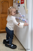 Almost 2 year old girl  wearing Grandma's shoes, at play with magnetic alphabet letters on her refrigerator.
