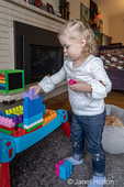 Almost 2 year old girl stacking blocks in a column