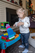 Almost 2 year old girl at play with blocks she has stacked, unsure of what to do as they are just about to fall over.