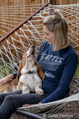 """Renton, Washington, USA.  Woman being affectionate with her five month old Basset Hound puppy """"Elvis"""" as they rest in a  hammock."""