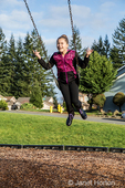 Issaquah, Washington, USA.  Ten year old girl swinging with no hands in a playground.  (MR)
