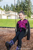 Issaquah, Washington, USA.  Ten year old girl sitting on a swing in a playground.  (MR)
