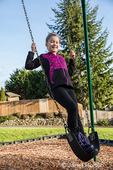 Issaquah, Washington, USA.  Ten year old girl standing on a swing in a playground.  (MR)