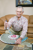 Man, Robert, doing toothbrush weaving, creating a rug, in his home