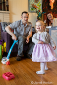 19 month old girl spinning in a circle as her parents look on laughing.  (MR)