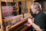 Man, Bruce, fixing broken thread on loom while weaving checkered dish towels on his AVL 16 shaft dobby loom in his home