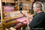 Man, Bruce, weaving checkered dish towels using fly shuttle on his AVL 16 shaft dobby loom in his home