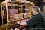 Man, Bruce, using hand shuttle in weaving checkered dish towels on his AVL 16 shaft dobby loom in his home