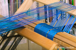 Close-up of the cotton warp in the double-back beam, that is a double-layer double weave, blue and black layers being woven.